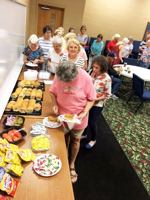 Seniors Line Up for Sandwiches and Chips at a Lunch and Learn Session