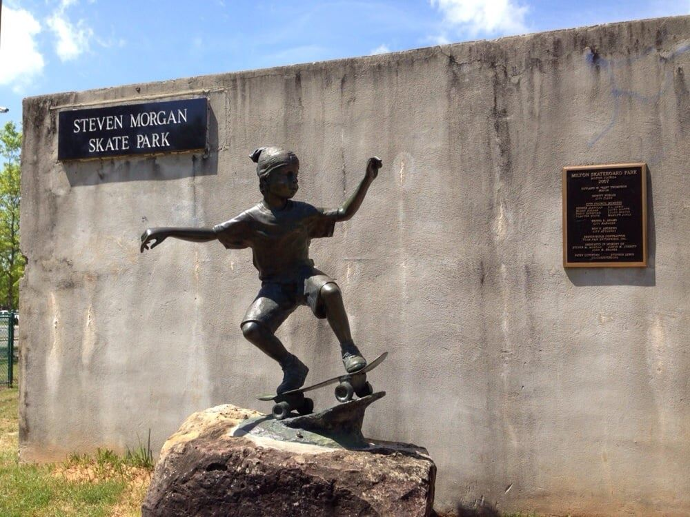 A statue of a young boy skateboarding in front of the Steven Morgan Skate Park