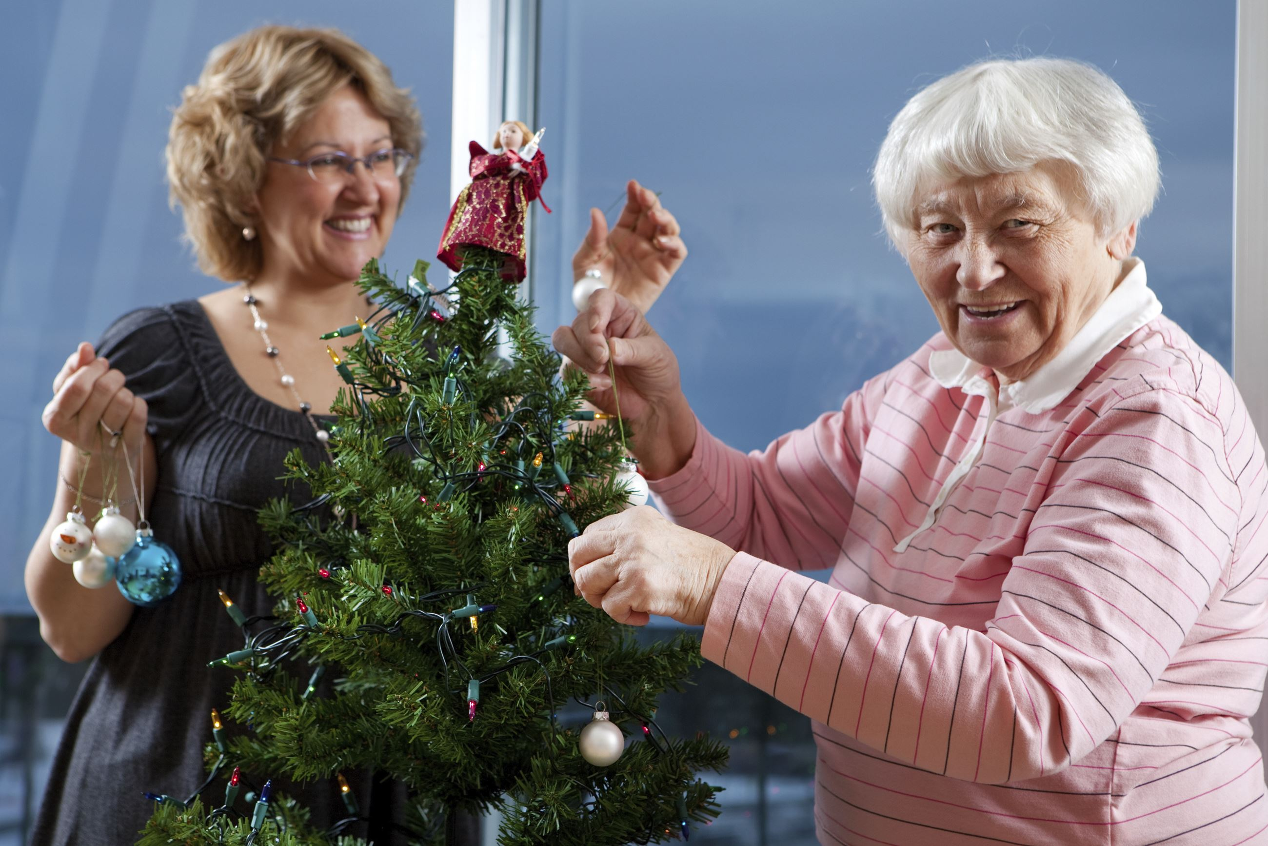 Two women decorate a Christmas tree
