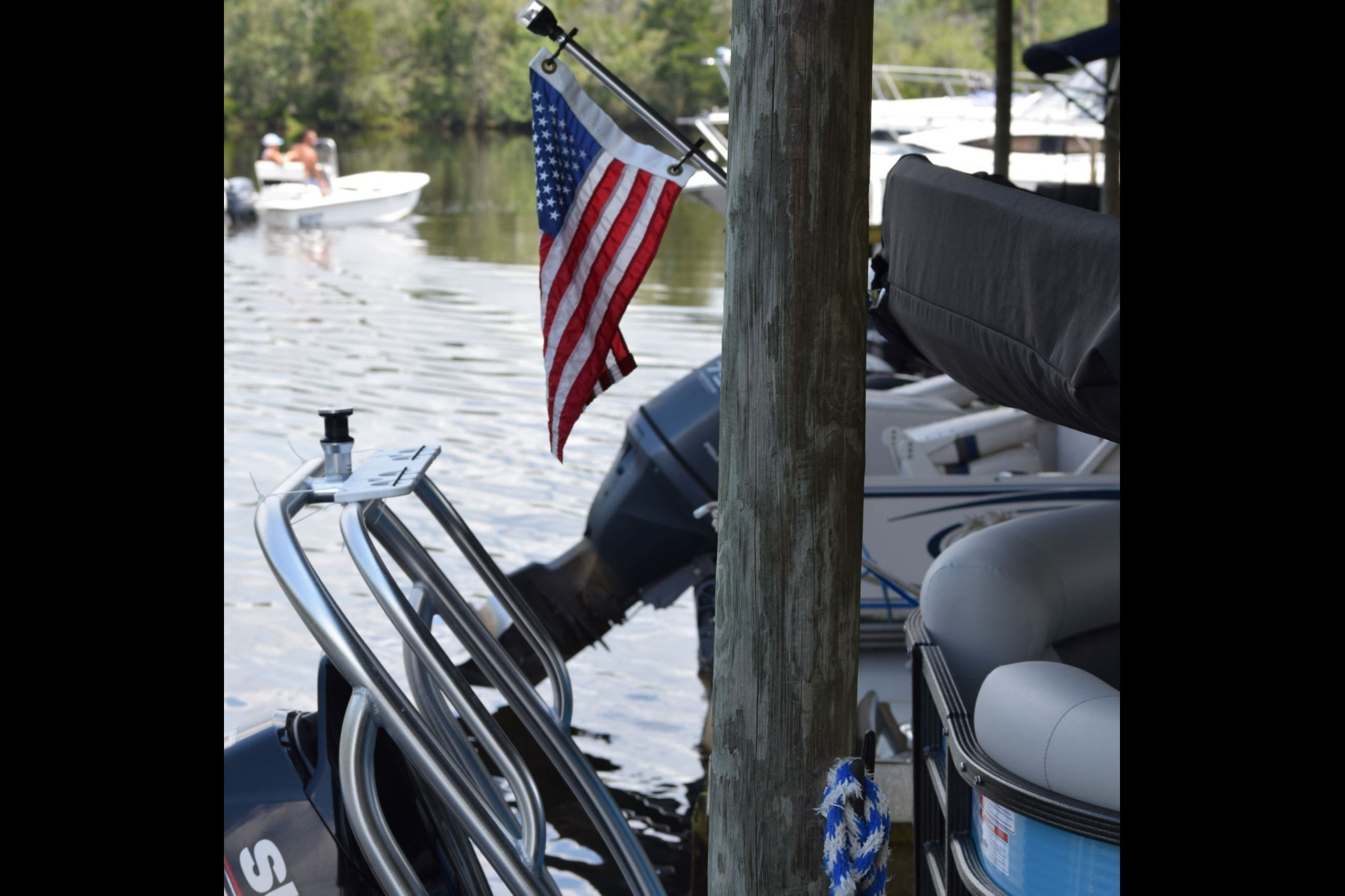 Wet slip at city marina with American flag and Blackwater River